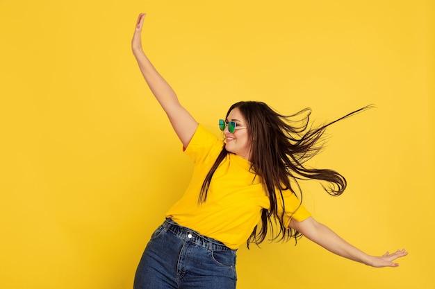Geïnspireerd dansen in zonnebril. blanke vrouw op gele muur. mooi vrouwelijk donkerbruin model in informele stijl. concept van menselijke emoties, gezichtsuitdrukking, verkoop, advertentie, copyspace.