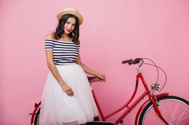Geïnspireerd europees meisje in lange rok die zich dichtbij fiets met glimlach bevindt. binnen schot van het elegante vrouwelijke model poseren.