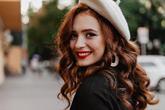 Geïnspireerd frans model dat op straat lacht. gember meisje in trendy baret buiten wandelen in herfstdag.