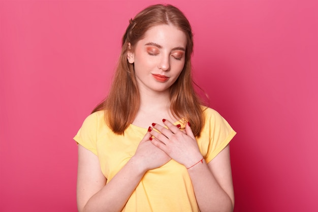 Geïnspireerd kalm roodharig wit meisje met rode lippenstift op haar lippen, manicure, make-up en mooi kapsel staat met gekruiste handen op haar hart met gesloten ogen, lijkt attent te zijn.