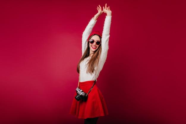Geïnspireerd kaukasisch meisje dansen met handen omhoog op bordeaux ruimte