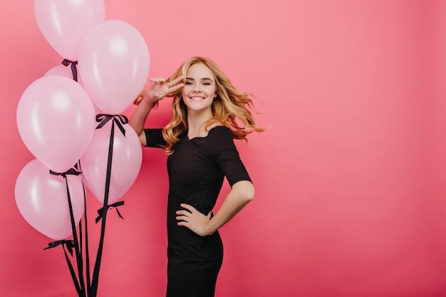 Geïnspireerd krullend feestvarken dat op roze muur danst. laughing extatische vrouw te wachten op gasten op haar feestje.