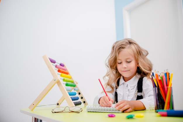 Geïnspireerd meisje aan de tafel met kleurpotloden. schoolbank met schoolbenodigdheden, potloden, tassen, scketchbook en telraam. weinig blond meisje die glazen terug naar schoolconcept dragen.