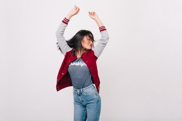 Geïnspireerd meisje draagt stijlvolle sport jas springen met handen omhoog geïsoleerd. opgewonden studente vrolijk dansen omdat ze een hoge score kreeg.