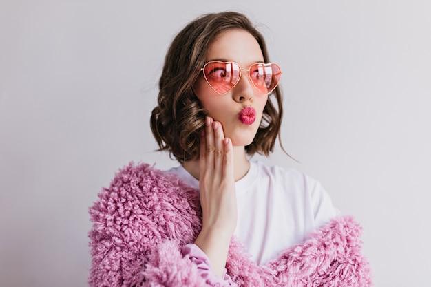 Geïnspireerd meisje in stijlvolle heldere zonnebril wegkijken met kussende gezichtsuitdrukking. grappig vrouwelijk model in bontjas gezichten maken tijdens fotoshoot op witte muur.