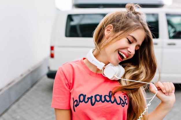 Geïnspireerd meisje met trendy kapsel genieten van goede dag met gesloten ogen en spelen met haar witte oortelefoons