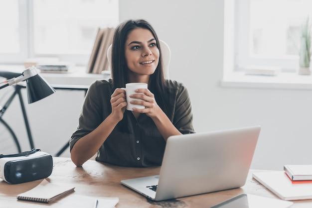 Geïnspireerd met kopje verse koffie. doordachte jonge vrouw in slimme vrijetijdskleding met koffiekopje en wegkijkend met een glimlach terwijl ze op haar werkplek op kantoor zit