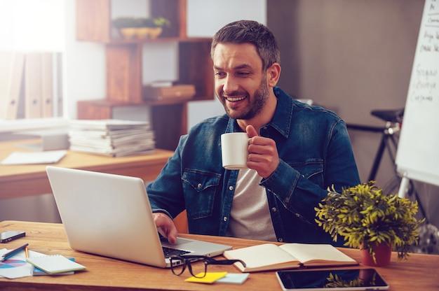Geïnspireerd met kopje verse koffie. zelfverzekerde jonge man die op laptop werkt en een koffiekopje vasthoudt terwijl hij op zijn werkplek op kantoor zit