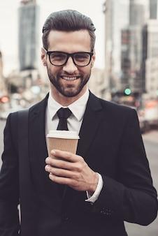 Geïnspireerd met kopje verse koffie. zelfverzekerde jonge man in volledig pak met koffiekopje