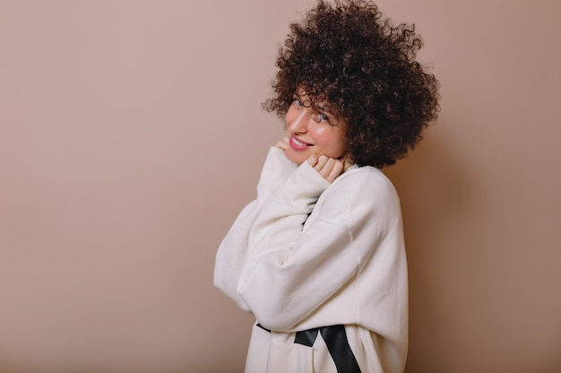 Geïnspireerd mooie jonge vrouw lachen in schattige pullover poseren op beige