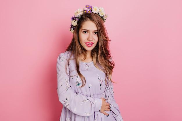Geïnspireerd vrouwelijk model draagt paarse kleding die naar de camera kijkt