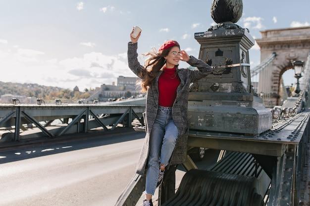 Geïnspireerd vrouwelijk model draagt vintage jeans die ontspant tijdens fotoshoot op de brug