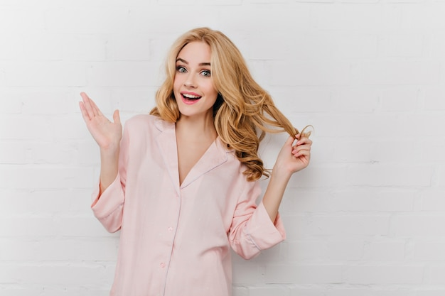 Geïnspireerd vrouwelijk model met blauwe ogen speelt met haar golvende haar. portret van knap meisje in roze pyjama's die pret in ochtend hebben.