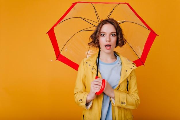Geïnspireerd wit meisje met verbaasde gezichtsuitdrukking die zich op gele muur met rode in hand parasol bevindt. foto van dromerige brunette dame in herfst kleding poseren met stijlvolle paraplu.