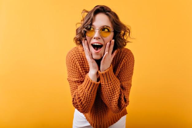 Geïnspireerd wit vrouwelijk model in vintage zonnebril wegkijken met een verbaasde glimlach