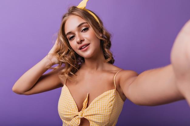 Geïnspireerd wit vrouwelijk model met trendy make-up selfie maken. jonge dame in gele kledij die met haar krullend haar speelt.
