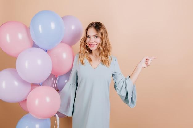 Geïnspireerd witte verjaardagsvrouw poseren met helium ballonnen