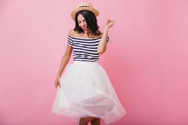 Geïnspireerd zwartharig meisje in strohoed dansen en zingen. binnenfoto van prachtige latijnse vrouw in weelderige rok.