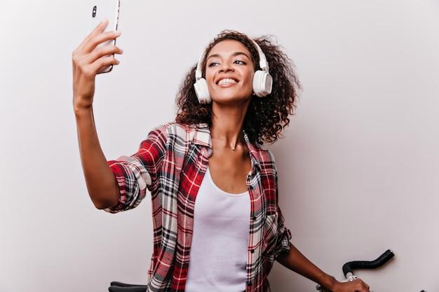 Geïnspireerde afrikaanse dame in witte koptelefoon die foto van zichzelf neemt. geïnteresseerd vrouwelijk model in geruit overhemd selfie met blij gezicht expressie maken.