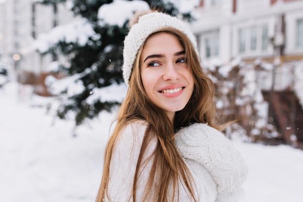Geïnspireerde blanke vrouw in wollen hoed wegkijken met glimlach terwijl poseren in winterochtend. close-upportret van fascinerende langharige vrouwelijk model in zachte witte sweater die zich in besneeuwde tuin bevinden.