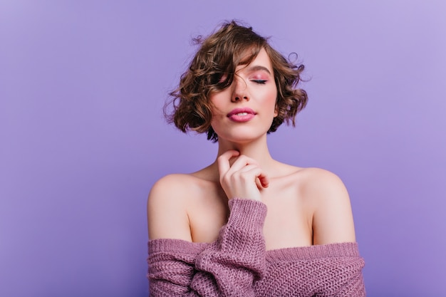 Geïnspireerde blanke vrouw met roze make-up poseren met gesloten ogen. indoor portret van korthaar meisje draagt trendy trui poseren op paarse muur.
