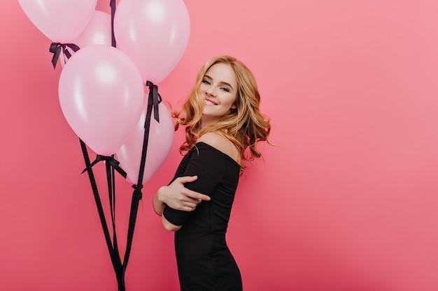 Geïnspireerde blonde vrouw in feestoutfit poseren in roze kamer met ballonnen op de muur. extatische blonde dame met een oprechte glimlach.