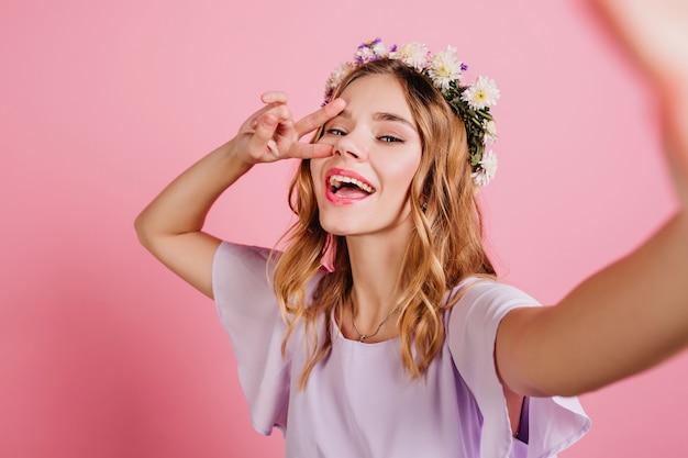 Geïnspireerde blonde vrouw in paarse kleding tijd doorbrengen in de studio