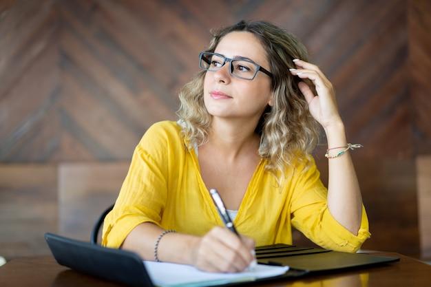 Geïnspireerde creatieve vrouw die ideeën neerschrijft