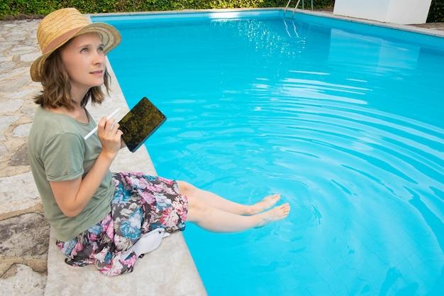Geïnspireerde creatieve vrouw in de zomer hoed zitten aan het zwembad