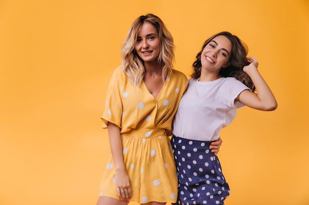 Geïnspireerde dame in gele kledij poseren met haar zus. indoor portret van enthousiaste vriendinnen met golvend haar.
