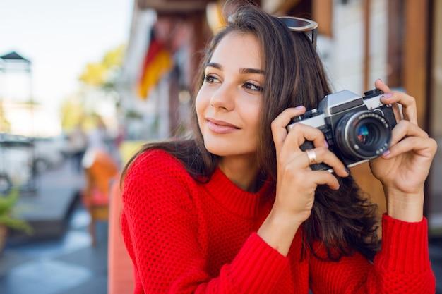 Geïnspireerde donkerbruine vrouw die pret heeft en foto's op haar vakanties maakt. koud seizoen. het dragen van stijlvolle rode gebreide trui.