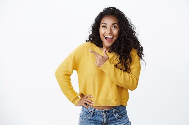 Geïnspireerde geamuseerde afro-amerikaanse vrouw gele trui hijgend geschokt en verbaasd, juichend emotioneel geweldig nieuws vertellend, hand taille vasthouden, naar links lege ruimte wijzend, staande witte muur