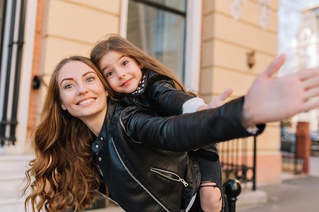 Geïnspireerde, gekrulde jonge vrouw zonder make-up die tijd doorbrengt met dochter en haar op de rug over de straat draagt. portret van geweldig klein meisje en haar stijlvolle trendy moeder zwaaiende hand op achtergrond wazig.