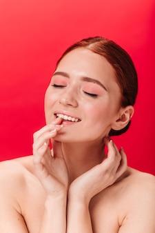 Geïnspireerde gember vrouw lippen aan te raken. studio shot van naakt vrouwelijk model poseren met gesloten ogen op rode achtergrond.