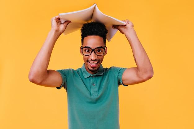Geïnspireerde internationale student die poseert tijdens de voorbereiding op examens. zorgeloze slimme afrikaanse kerel die na de lessen chant.