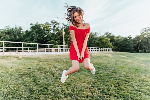 Geïnspireerde jonge vrouw die in park springt en glimlacht. mooie brunette meisje in een rode jurk plezier in zomerweekend.