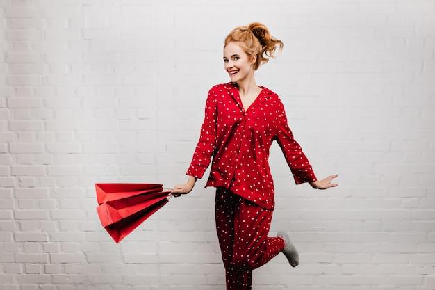 Geïnspireerde jonge vrouw die met een papieren zak energie uitdrukken. binnenfoto van dame met golvend haar draagt rode pyjama met nieuwjaarscadeau.