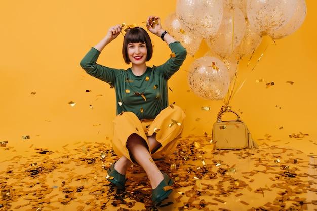 Geïnspireerde jonge vrouw die op verjaardag voor de gek houdt. indoor foto van brunette fascinerende meisje, zittend op de vloer met ballonnen.