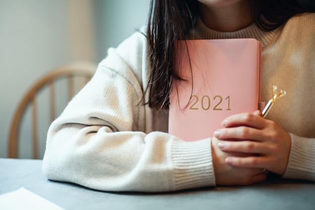 Geïnspireerde jonge vrouw met een glimlach die door het raam kijkt en een koraalkleurig dagboek vasthoudt 2021