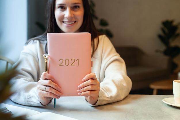 Geïnspireerde jonge vrouw met een glimlach die door het raam kijkt en koraalkleurig dagboek vasthoudt 2021. hoop en inspiratie concept. dame glimlacht en droomt over toekomstig nieuwjaar. geluk en succes.