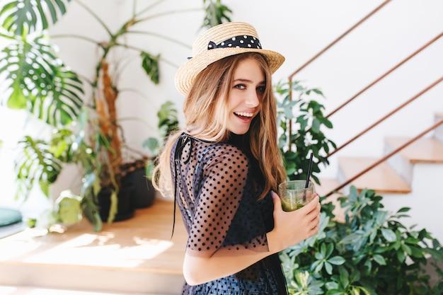 Geïnspireerde jonge vrouw met lang glanzend haar kijkt over schouder en lachend glas koude drank te houden