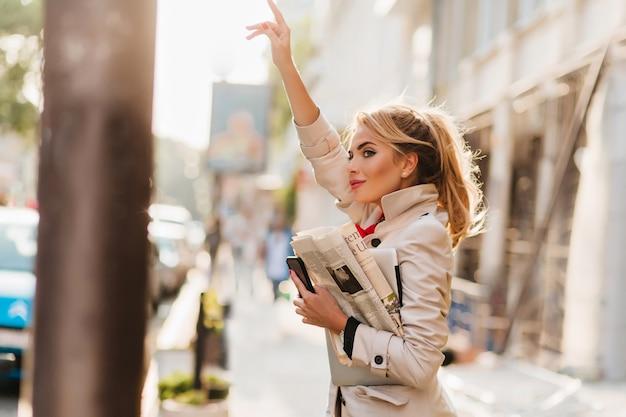 Geïnspireerde jonge zakenvrouw die zich naar de werkplek haast en taxi op straat vangt