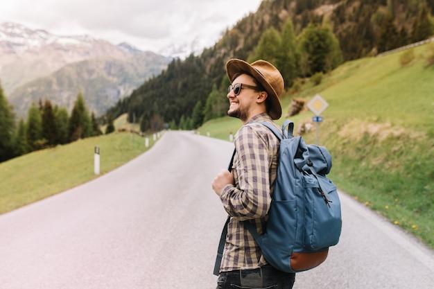 Geïnspireerde jongeman met een oprechte glimlach die rondkijkt en geniet van de geweldige italiaanse natuur en het boslandschap
