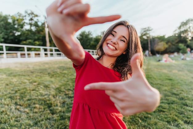 Geïnspireerde knappe vrouw die danst met een vrolijke glimlach. prachtig donkerharig meisje dat geniet van fotoshoot buitenshuis.