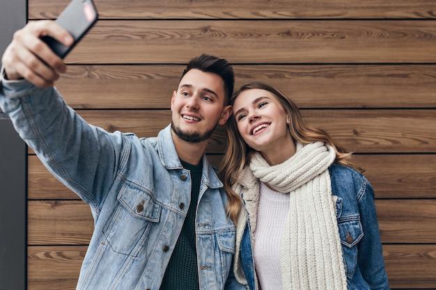 Geïnspireerde man met baard selfie maken met zijn vriendin. prachtige jonge vrouw met zwarte sjaal poseren op houten muur.