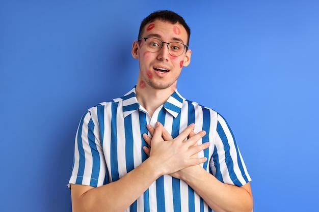 Geïnspireerde man met sporen van kus op wang met handen op de borst