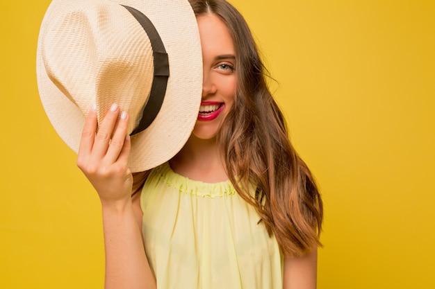 Geïnspireerde mooie vrouw met lang golvend haar dat haar gezicht bedekt met hoed