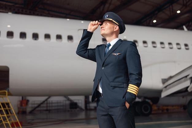 Geïnspireerde piloot in uniform die wegkijkt, zijn hoed aanpast, voor een groot passagiersvliegtuig in de luchthavenhangar staat. vliegtuigen, beroep, transportconcept