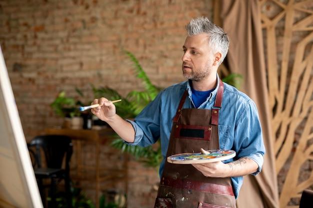 Geïnspireerde schilder met penseel en palet die onafgemaakt schilderij bekijkt terwijl hij in zijn atelier werkt