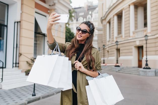 Geïnspireerde shopaholic vrouw met gebruinde huid selfie maken in weekend